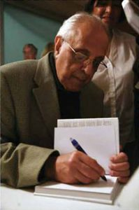 Photo of Ahmed 'Kathy' Katnrada signing books