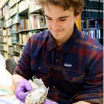 Oliver Autrey handles a collection item with gloves at the MSU Museum