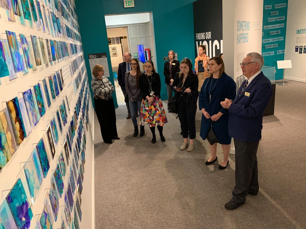 "Representative Elissa Slotkin viewing the ""Finding Our Voice: Sister Survivors Speak"" exhibit"