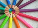 14 colored pencils in rainbow colors laid tip to tip forming a starburst shape