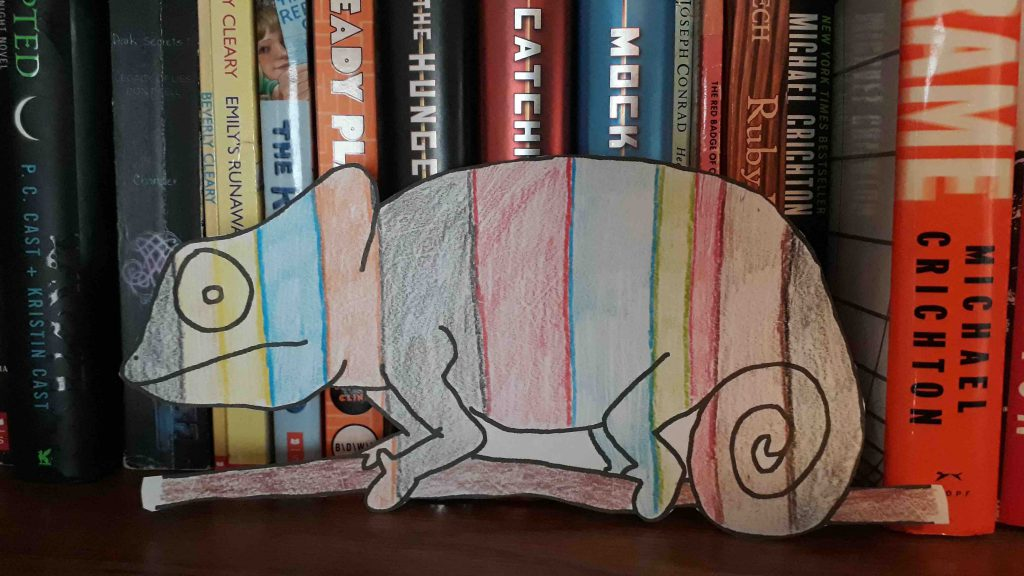 Paper drawing of chameleon colored to blend into books on a shelf