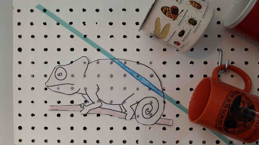 Paper drawing of chameleon colored to blend into pegboard