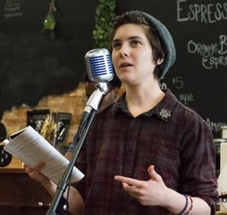 Person reading poetry in front of a microphone at coffee house